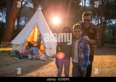 Schüler und Lehrer lächelnd auf Campingplatz - Stockfoto