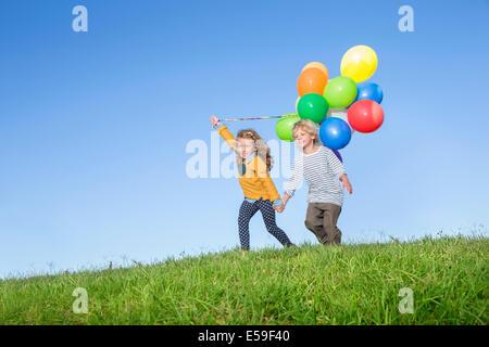 Kinder mit Haufen Luftballons auf grasbewachsenen Hügel - Stockfoto