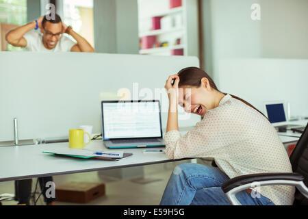 Frau am Laptop im Büro arbeiten - Stockfoto