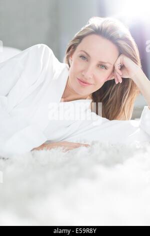 Frau im Bademantel auf Bett - Stockfoto