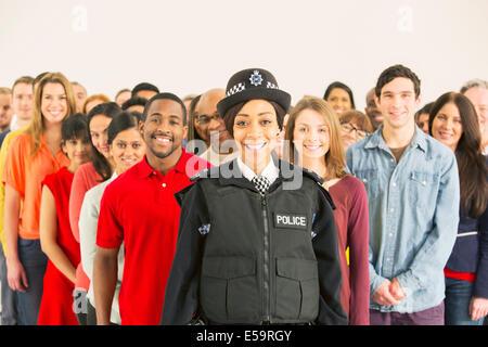 Porträt von lächelnden Polizistin vor großen Publikum - Stockfoto