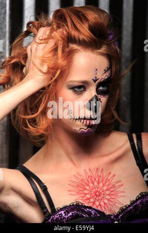 Eine junge Frau mit Bemalung in Form eines Schädels Zucker dekoriert für Dia de Los Muertos - Stockfoto