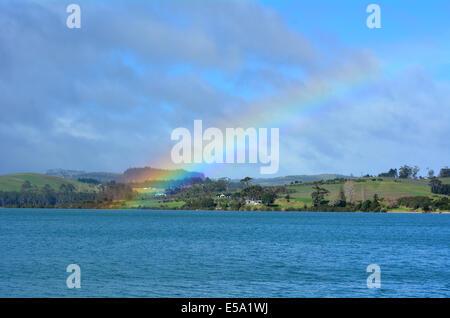 Regenbogen am Himmel und über dem Meer und grünen Hügeln. - Stockfoto