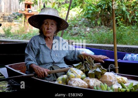 Alte Frau Verkauf von Obst und Gemüse. Damnoen Saduak Floating Market in der Nähe von Bangkok, Thailand, Südostasien - Stockfoto