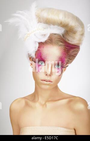 Faceart. Blondine mit Haut rosa gefärbt, falsche Wimpern und weiße Feder - Stockfoto