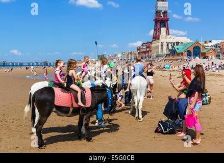 Eselreiten am Strand mit Blick auf North Pier und Blackpool Tower, The Golden Mile, Blackpool, Lancashire, UK - Stockfoto