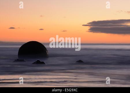 Sonnenaufgang am Koekohe Strand mit einem Moeraki Boulder - Stockfoto