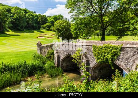 Eine steinerne Fußgängerbrücke über den Fluss von Bach mit einem Golfplatz jenseits. - Stockfoto