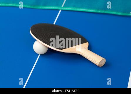 schwarzen Tischtennisschläger auf a blaue Tabelle mit grünen net im Hintergrund - Stockfoto