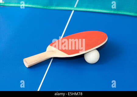 roten Tischtennisschläger auf a blaue Tabelle mit grünen net im Hintergrund - Stockfoto