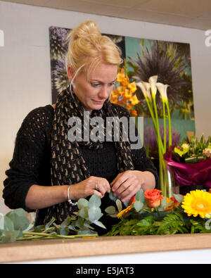 Floristen arrangieren einen Kranz in einem Blumenladen mit Trauben von Blumen und eine Blume Poster im Hintergrund. - Stockfoto