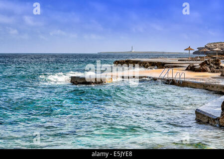 Blick auf S´Algat Strand von Menorca mit Leuchtturm im Hintergrund, Balearen, Spanien - Stockfoto