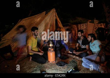 Gaza-Stadt, Gaza-Streifen. 2. August 2014. Vertriebene Palästinenser sitzen vor einem provisorischen Zelt am 2. August 2014 an al-Shifa-Krankenhauses in Gaza-Stadt, wo Familien Zuflucht gefunden, nach der Flucht aus ihrer Heimat in einem Bereich unter schweren israelischen Militärschläge in dem besetzten Gebiet, am 2. August 2014. Bildnachweis: ZUMA Press, Inc./Alamy Live-Nachrichten