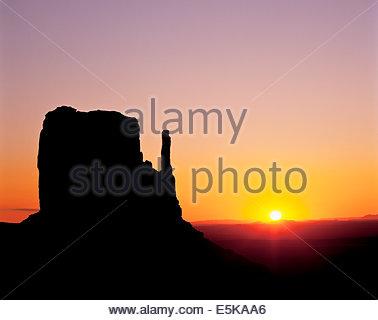 Sonnenaufgang hinter dem West Mitten Butte im Monument Valley, einem Navajo Tribal Park im Navajo Reservat in Arizona - Stockfoto