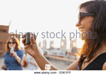 Lächelnde Frau fotografieren auf städtischen Dach party - Stockfoto
