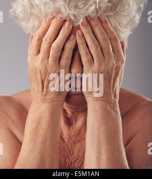 Close-up Portrait einer traurig aussehende senior Frau mit dem Kopf in die Hände vor grauem Hintergrund. Verärgert - Stockfoto