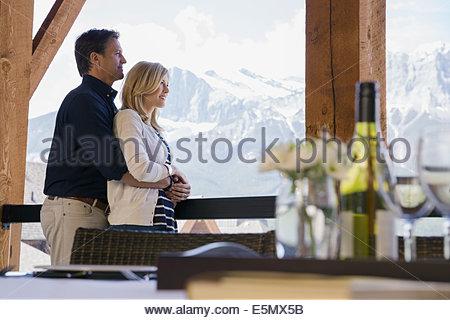 Paar umarmt auf Balkon mit Bergblick - Stockfoto
