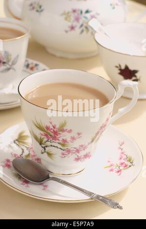 Der Nachmittagstee serviert in Vintage floral nicht übereinstimmende Tassen und Untertassen - Stockfoto