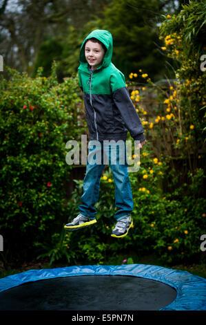 Junge im Anorak auf Trampolin springen - Stockfoto