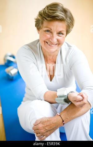 Senior Frau, die ihren Blutdruck mit ein tragbares Blutdruckmessgerät. - Stockfoto