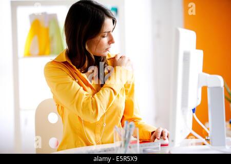 Frau mit einem Gelenk Schmerzen im Büro. - Stockfoto