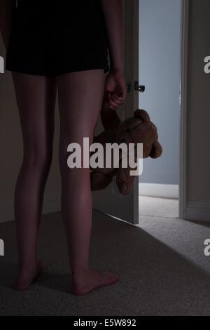Anonyme junges Mädchen steht vor einer offenen Tür hält einen Teddybären in einem dunklen Raum. - Stockfoto