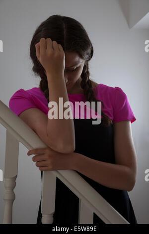 Junge Frau hand trägt ein pinkes Top und Haar in Plats stehend auf der Treppe im Innenbereich, aufs Gesicht. - Stockfoto