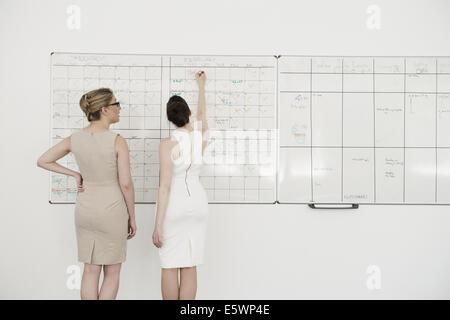 Zwei junge Unternehmerinnen Planung auf Büro whiteboard - Stockfoto