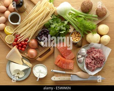 Auswahl von frischen Rohkost mit Eiern, Nudeln, Kräuter, Käse, Gemüse, Lachs und gehacktem Schweinefleisch - Stockfoto