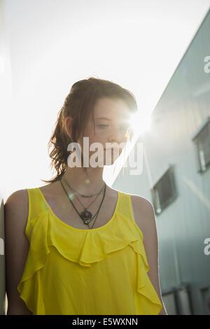 Mürrisches Mädchen in gelben Bluse blickt nach unten - Stockfoto