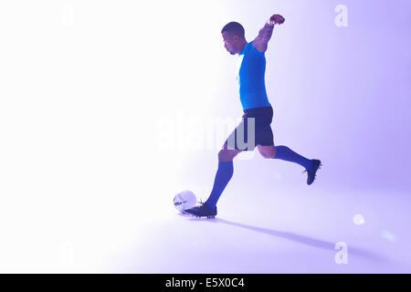 Studioaufnahme des jungen männlichen Fußballer mit Arme ausgestreckt, den Ball - Stockfoto