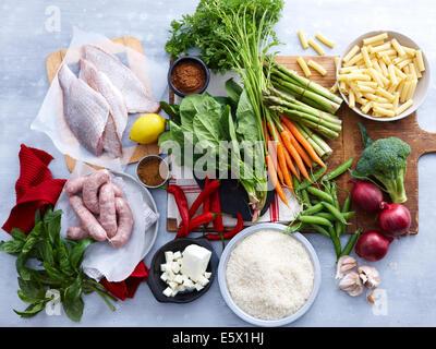 Draufsicht auf Fisch, Wurst, Feta und Auswahl an frischen Bio-Kräuter und Gemüse - Stockfoto