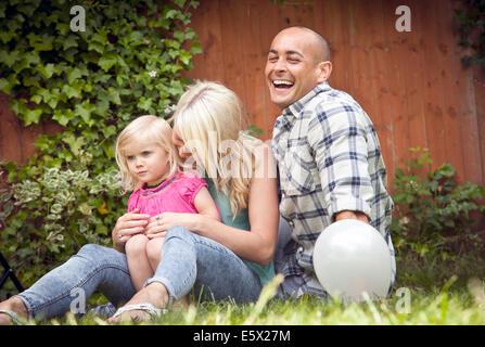 Glückliches Paar mit Kleinkind Tochter im Garten sitzen - Stockfoto