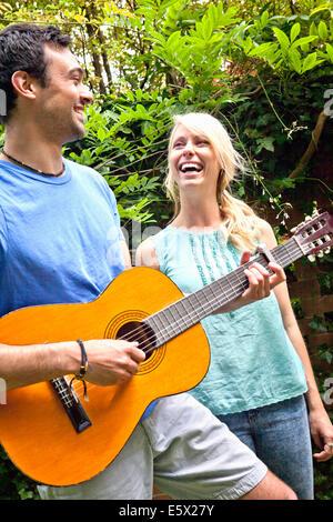 Junger Mann spielt akustische Gitarre im Garten für Freundin - Stockfoto
