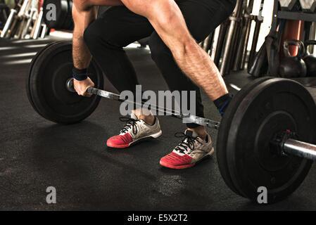 Bodybuilder, die Biegung um die Hantel heben Sie im Fitness-Studio - Stockfoto