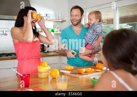 Mutter macht ein Gesicht mit Orangen für ihre Familie am Frühstücks-bar