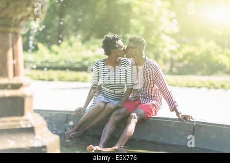 Junge Paar küssen mit nackten Füßen in Bethesda Brunnen, Central Park, New York City, USA - Stockfoto