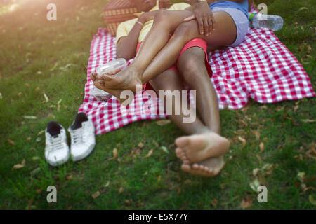 Bild des jungen Paares im liegen im Park auf der Picknickdecke beschnitten - Stockfoto