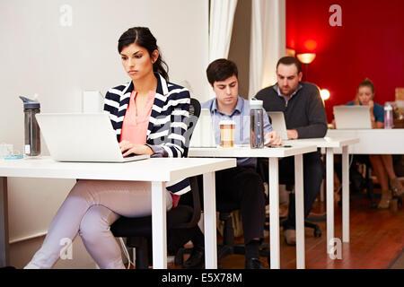 Reihe von Menschen, die auf Laptops im Büro - Stockfoto