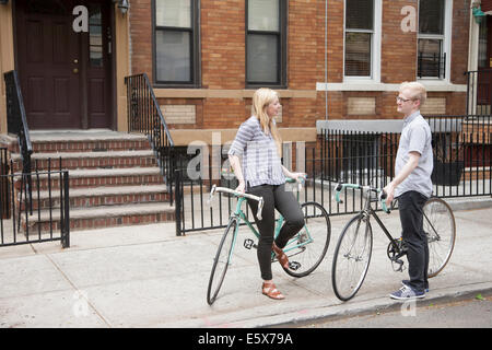 Junges Paar mit Fahrrädern, die im Chat auf Straße - Stockfoto