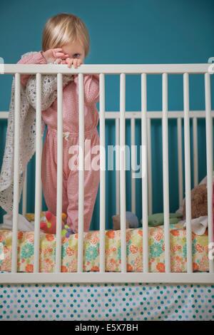 Porträt von weiblichen Kind versteckt sich hinter Schmusedecke in Krippe - Stockfoto
