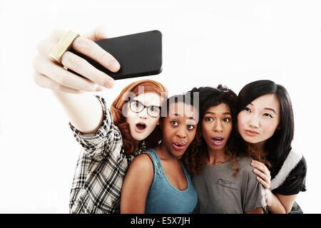 Studio-Porträt von vier jungen Frauen, die die Selfie auf smartphone - Stockfoto