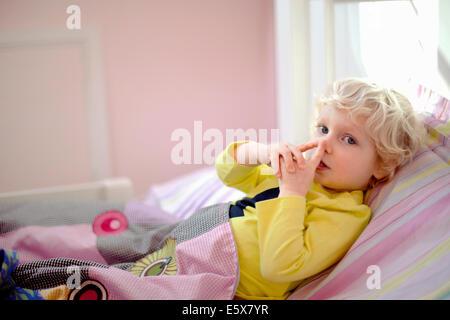 Männliche Kleinkind liegend im Bett machen geheime Geste Handzeichen - Stockfoto