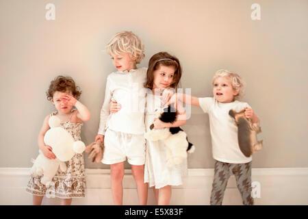 Porträt von vier kleinen Kindern in einer Reihe, man weint - Stockfoto