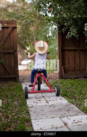 Vier Jahre altes Mädchen reiten ihr Dreirad aus Gartentor - Stockfoto