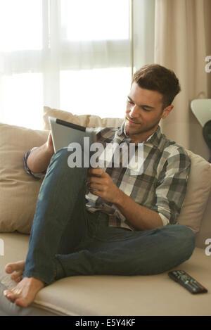 mann auf sofa mit digitalen tablet und smartphone. Black Bedroom Furniture Sets. Home Design Ideas