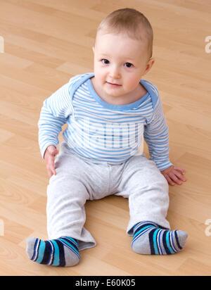 schöne lachende Baby Junge sitzt - Stockfoto