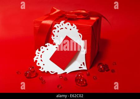 Niedlichen roten Kasten mit Pfeil und Bogen Glas glänzend Herz, weiß Valentines Spitze Herz mit Karte für Text auf - Stockfoto