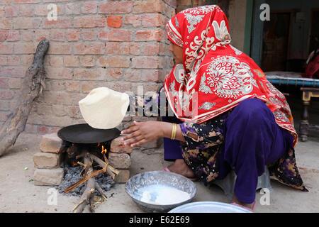 Frau in traditioneller Kleidung Roti Brot (auch bekannt als Chapati) am offenen Feuer backen. Khushpur Dorf, Provinz - Stockfoto