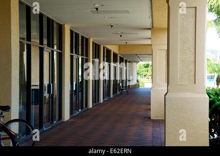 Auf der Suche nach unten eine Reihe von Schaufenster an einer Mall in Florida, leere Parkbank mit dem Fahrrad. - Stockfoto